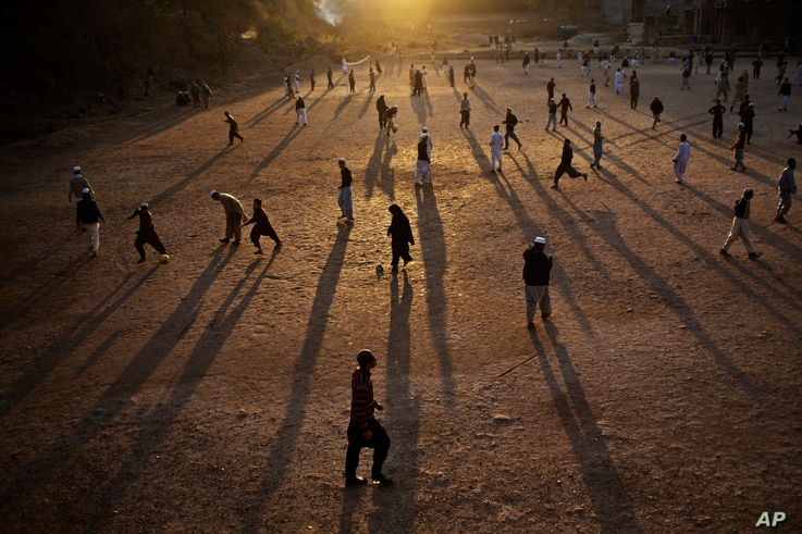 In this Jan. 27, 2015, photo, Pakistani students of a madrassa play football in their seminary's yard as the sun sets on the outskirts of Islamabad, Pakistan.