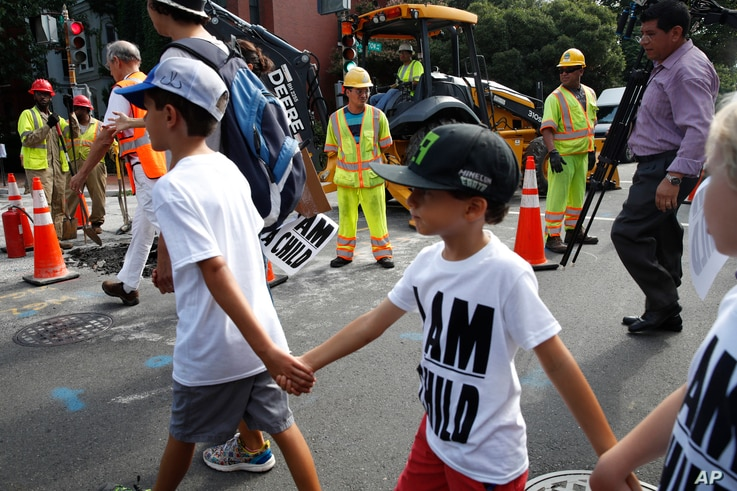 Construction workers watch as children hold hands during a march in protest of the separation of immigrant families, July 26, 2018, on Capitol Hill in Washington.