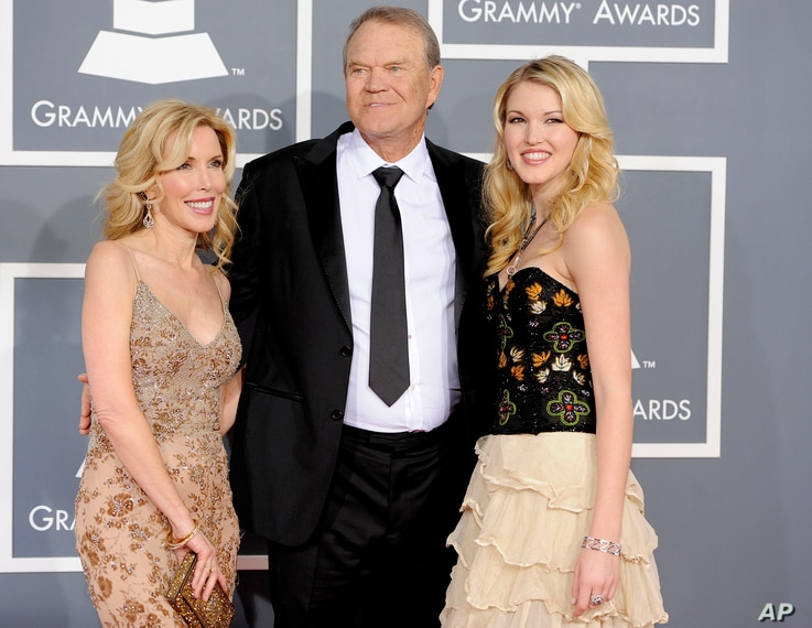FILE - Glen Campbell, center, Kim Woolen, left, and Ashley Campbell arrive at the 54th annual Grammy Awards in Los Angeles, Feb. 12, 2012.