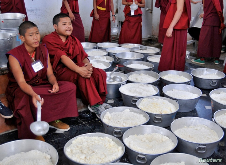 Young Buddhist monks wait to serve cooked rice to the attendees of the Jangchup Lamrim teachings conducted by the exiled Tibetan spiritual leader the Dalai Lama (unseen) at the Gaden Jangtse Thoesam Norling Monastery in Mundgod in the southern Indian...