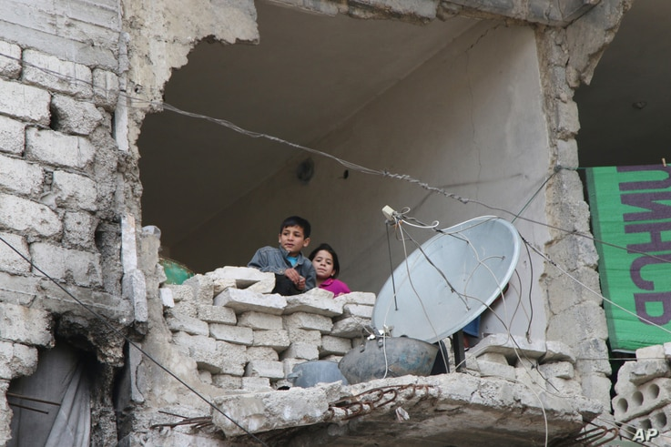 FILE - children peer from a partially destroyed home in Aleppo, Syria.