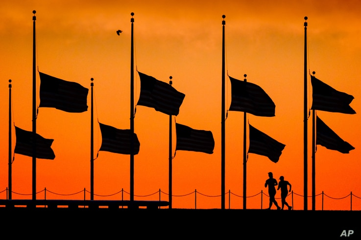 Runners pass under the the flags flying at half-staff around the Washington Monument at daybreak in Washington, Monday, June 13, 2016. The flags were ordered to half-staff by President Barack Obama to honor the victims of the Orlando nightclub shooti...