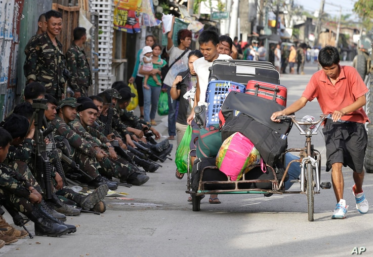 Residents who abandon their homes, carry their belongings as about 200 Muslim rebels, enraged by a broken peace deal with the Philippine government, held scores of hostages as human shields Tuesday Sept. 10, 2013 in a standoff with government forces