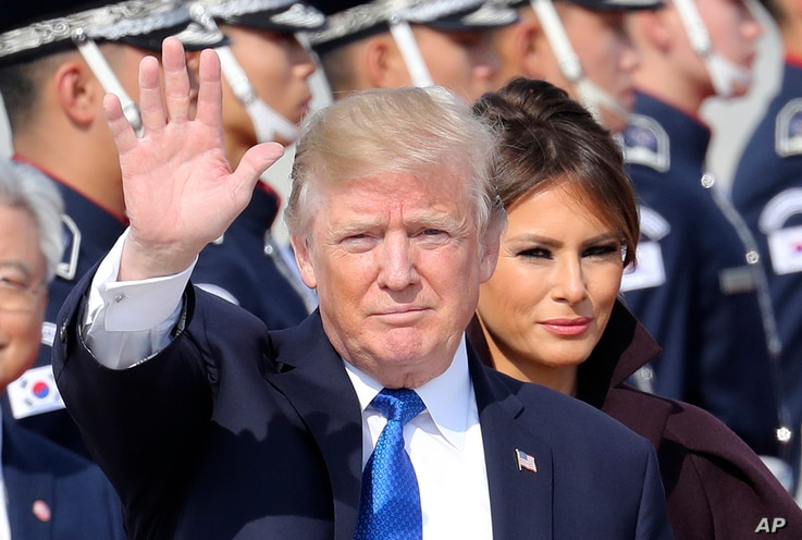 U.S. President Donald Trump waves as first lady Melania Trump, center right, stands upon their arrival at Osan Air Base in Pyeongtaek, South Korea, Tuesday, Nov. 7, 2017.