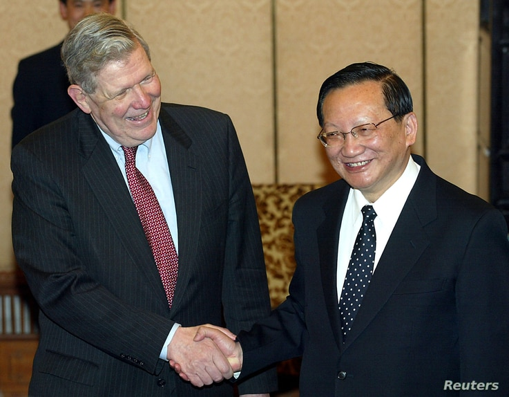 FILE - U.S. Assistant Secretary of State James Kelly (left) shakes hands with Chinese State Councillor and former foreign minister Tang Jiaxuan in Beijing Feb. 26, 2004.