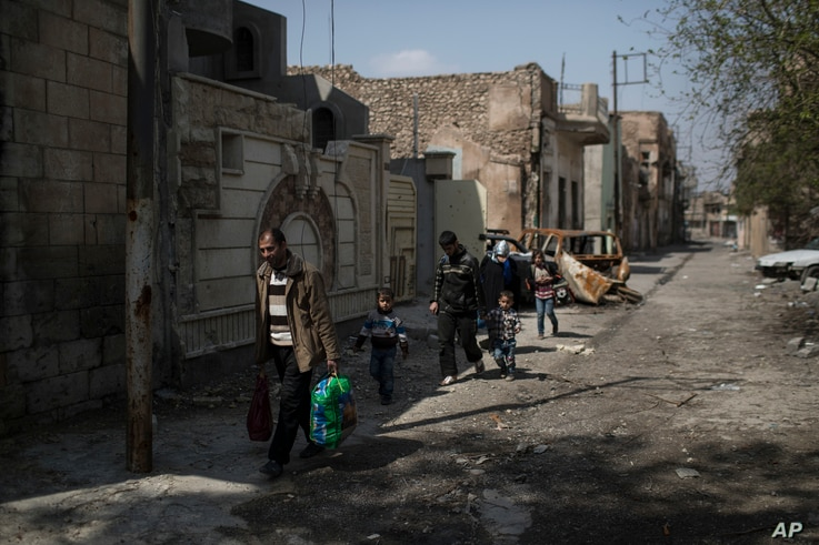 Mustafa Ismael Mustafa flees with his family for the second time during fighting between Iraqi forces and Islamic State militants, on the western side of Mosul, Iraq.