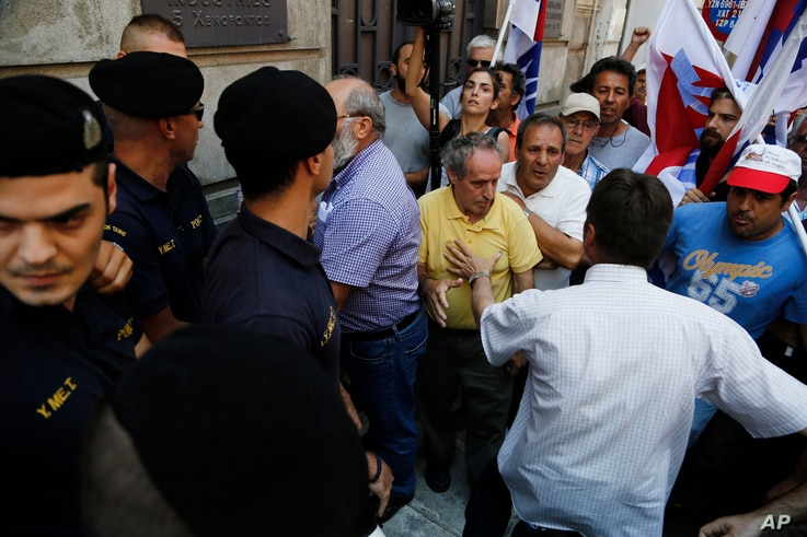 Members of the Communist-affiliated PAME labor union jostle next of riot police outside of the a Federation of Greek Industries during an anti-austerity protest in central Athens, on Friday, July 3, 2015. Greece braced for more chaos on the streets o...