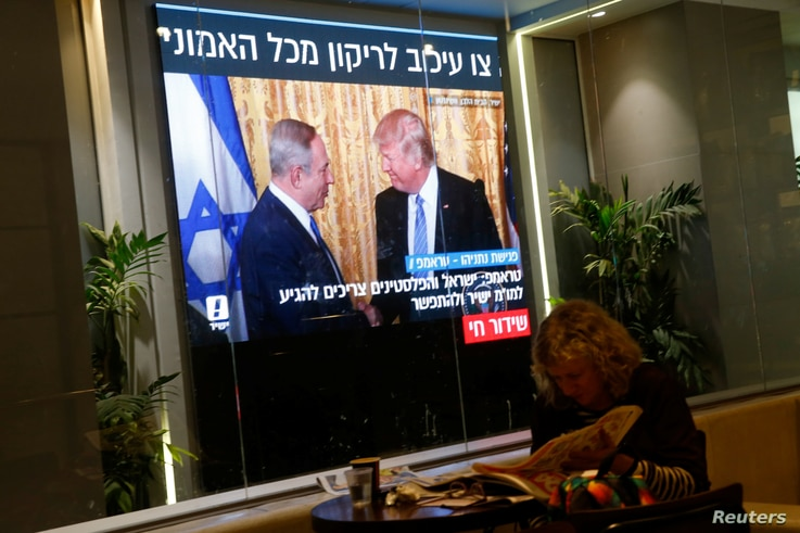 A woman reads a newspaper as monitors showing the meeting between U.S. President Donald Trump and Israeli Prime Minister Benjamin Netanyahu in Washington, are seen next to a coffee shop in Tel Aviv, Israel February 15, 2017.