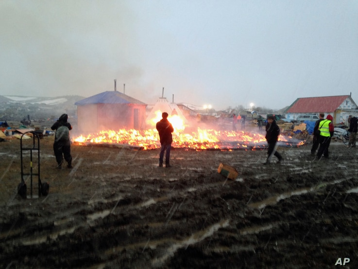 Dakota Access pipeline opponents burn structures in their main protest camp in southern North Dakota near Cannon Ball, N.D., Feb. 22, 2017, as authorities prepare to shut down the camp in advance of spring flooding season.
