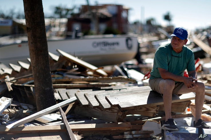 """Hector Morales sits on a debris pile near his home which was destroyed by Hurricane Michael, in Mexico Beach, Florida, Oct. 12, 2018. """"I have nothing else to do. I'm just waiting,"""" said Morales as he wonders what he will do next. """"I lost everything.""""..."""