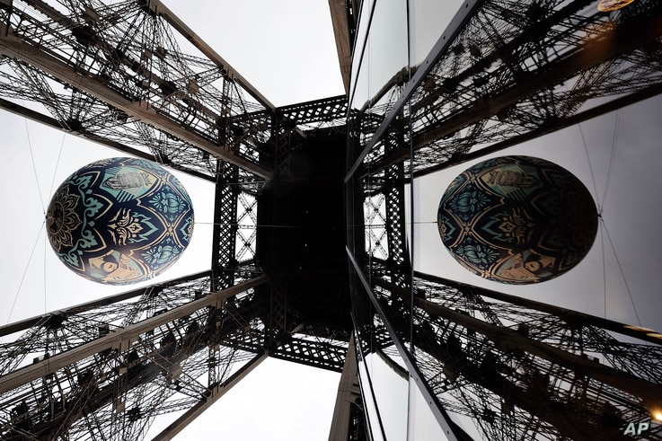 American street artist Shepard Fairey's (aka Obey) latest piece 'Earth Crisis,' a giant sphere themed on environment and hanging between the first and second floor of the Eiffel Tower in Paris, Nov. 20, 2015.