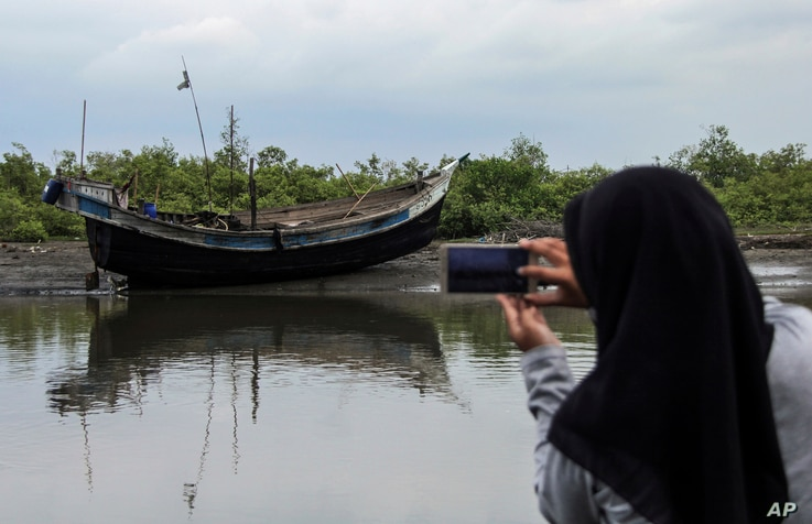 FILE - An Acehnese woman uses her mobile phone to take pictures of the boat carrying a group of ethnic-Rohingya that was brought ashore in Bireuen, Aceh province, Indonesia, April 20, 2018.