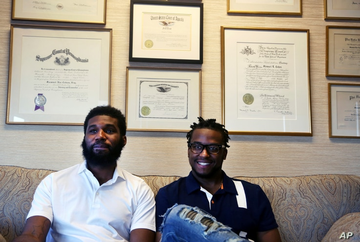 Rashon Nelson, left, and Donte Robinson, right, sit on their attorney's sofa following an interview with The Associated Press in Philadelphia, April 18, 2018.