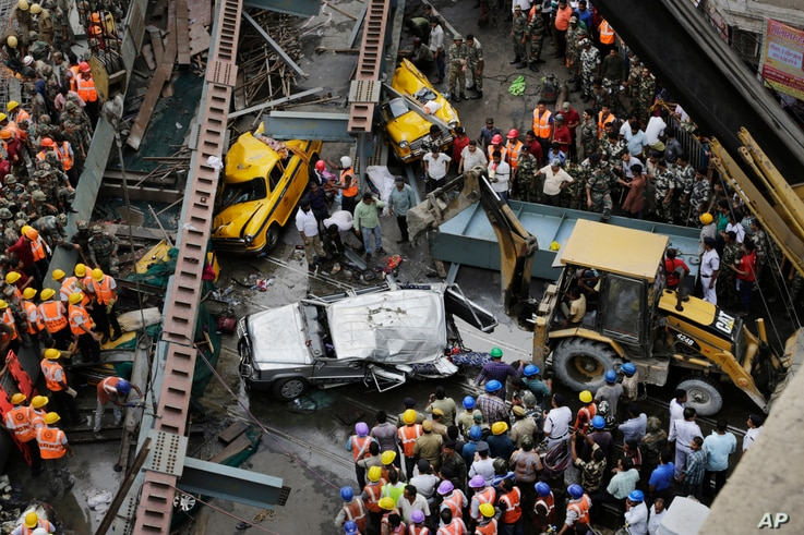 Rescue workers work at the site of a partially collapsed overpass in Kolkata, India, March 31, 2016.