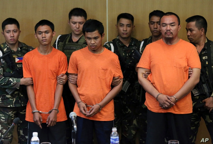 Suspected Muslim extremists, from left in front row, Wendel Apostol Facturan, Musali Mustapha and TJ Tagdaya Macabalang are presented to reporters at Camp Aguinaldo military headquarters in Quezon city, north of Manila, Philippines, Oct. 7, 2016.
