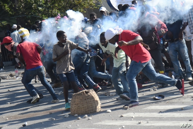 A tear gas canister, fired by the police, hits protesters during the clashes in front of the National Palace, in the center of Haitian capital Port-au-Prince, Feb. 13, 2019, on the sixth day of protests against Haitian President Jovenel Moise.