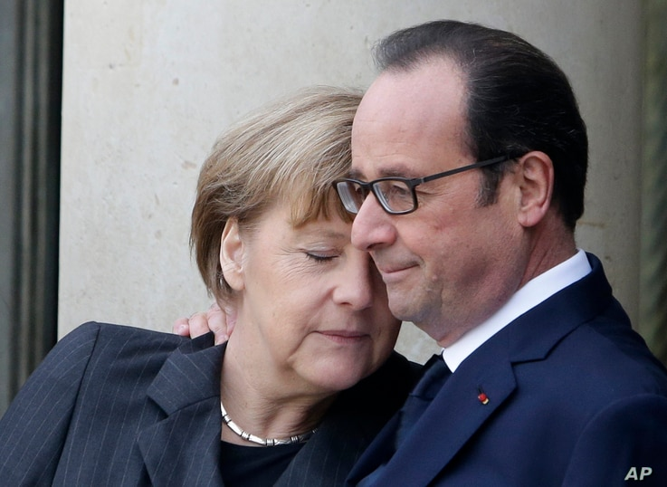 French President Francois Hollande embraces German Chancellor Angela Merkel, left, as she arrives at the Elysee Palace, Paris, Sunday, Jan. 11, 2015.