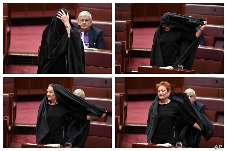 In this combination of photos Sen. Pauline Hanson takes off a burqa she wore into the Senate chamber at Parliament House in Canberra, Australia, Aug. 17, 2017.