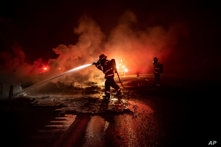 A firefighter sprays the smoldering remains of a vehicle on Interstate 5 as the Delta Fire burns in the Shasta-Trinity National Forest, Calif., on Sept. 5, 2018.
