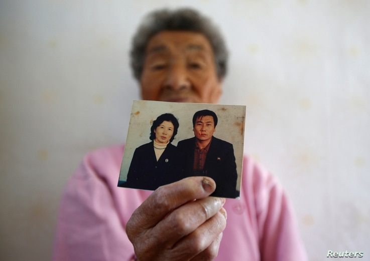 FILE - Park Gyu-soon, whose two sons were abducted in 1972 by North Koreans, poses for photographs with a picture of her second son (R) at her house in Nongso village in Geoje, October 29, 2013.