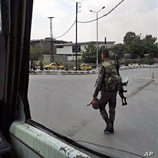 In this photo taken on a mobile phone, a Syrian soldier patrols streets in Damascus on May 8, 2011