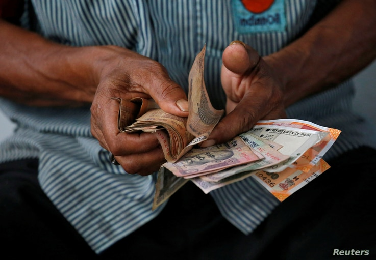 An attendant at a fuel station arranges Indian rupee notes in Kolkata, India, Aug. 16, 2018.