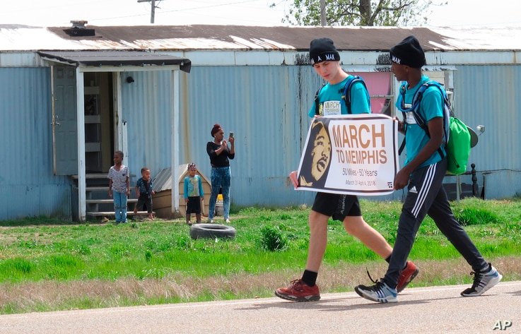 Two teenagers from Mississippi walk along U.S. Highway 61 during a 50-mile march to Memphis, Tennessee, as a tribute to slain civil rights leader Martin Luther King Jr., March 31, 2018, in Dundee, Miss. They are part of a group of six teens who plan...