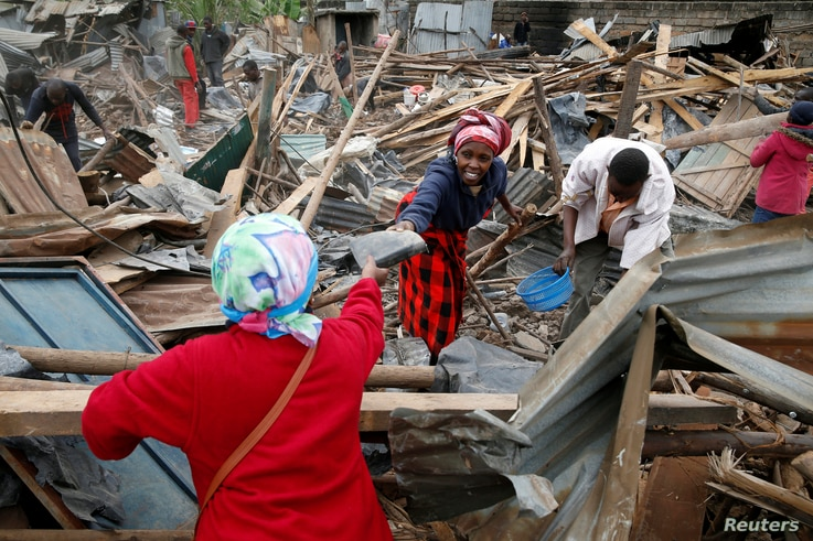 Catharine Kamiri (L) and her sister Mercy Wanjiku (C) collect the remainings of their belongings after bulldozers demolished their house to make way for a new road in the Kibera slum in Nairobi, Kenya, July 23, 2018.