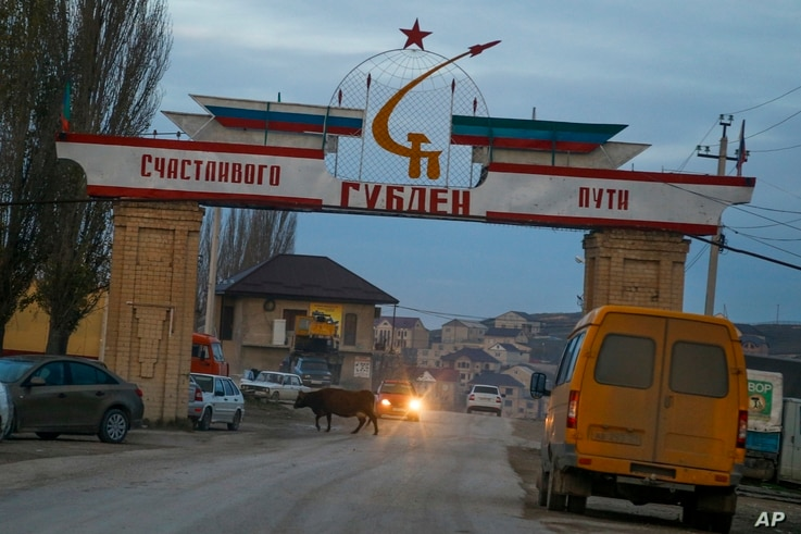 "An entrance to the village of Gubden with a sign reading ""Happy Travel. Gulden"" is decorated with banner in colors of Russian and Dagestani flags,  in the village of Gubden, Dagestan, Russia, Nov. 15, 2015."