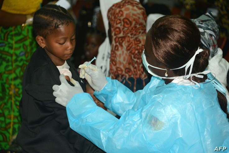 FILE - A Cameroonian nurse gives an injection to a girl arriving with her familly after spending several months in Libya, at the Yaounde International Airport in Cameroon, Nov. 22, 2017.