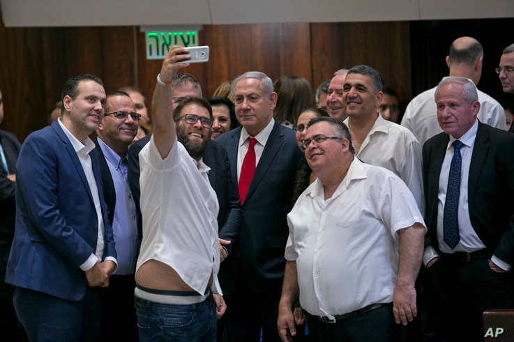 Knesset member Oren Hazan takes a selfie with Israel's Prime Minister Benjamin Netanyahu, center, and MP David Bitan, right of Netanyahu, after a Knesset session that passed of a contentious bill, in Jerusalem, Thursday, July 19, 2018. Israel's parli...