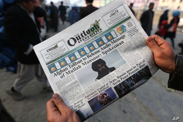 FILE - An Afghan man reads a local newspaper with photos of Afghan Taliban leader Mullah Akhtar Mansour, in Kabul, Afghanistan, Dec. 6, 2015. The U.S. military said a drone strike Friday has likely killed Mansoor in a remote area of Pakistan near Afg...