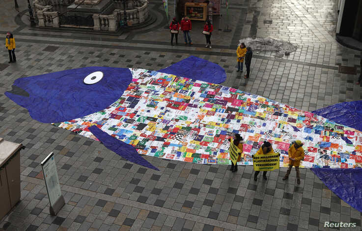 Some 800 shopping bags made of plastic sewed together in the shape of a fish are laid out by environmental activist group Greenpeace, in a protest against the pollution of oceans by plastic, in a street in Vienna January 29, 2015.   REUTERS/Heinz-Pet