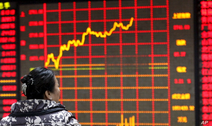 An investor looks at an electronic board showing stock information at a brokerage house in Huaibei, Anhui province, Jan. 29, 2016.