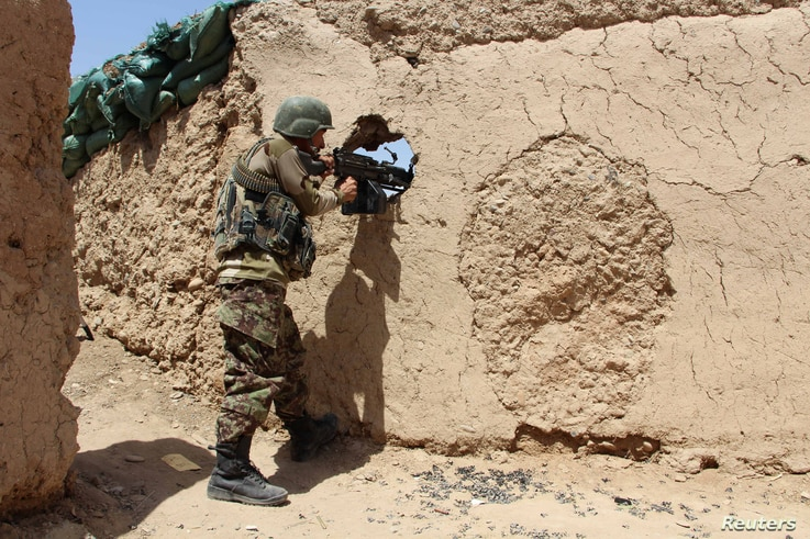 FILE - An Afghan National Army (ANA) soldier mans his position at an outpost in Babaji area of Lashkar Gah Helmand province, Afghanistan.