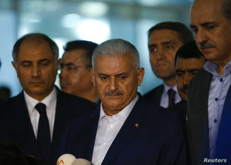 Turkey's Prime Minister Binali Yildirim, center, speaks to reporters next to Interior Miinister Efkan Ala, left, at the Ataturk airport in Istanbul, Turkey, following a multiple suicide bombing, June 29, 2016.