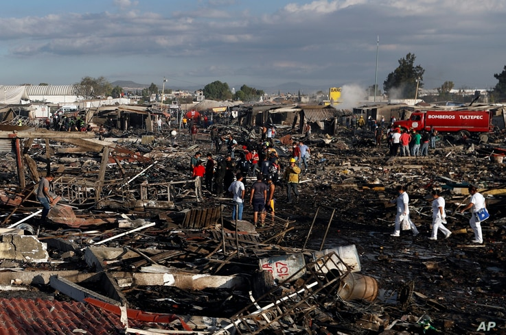 Firefighters and rescue workers walk through the scorched ground of Mexico's best-known fireworks market after an explosion explosion ripped through it, in Tultepec, Mexico, Dec. 20, 2016.