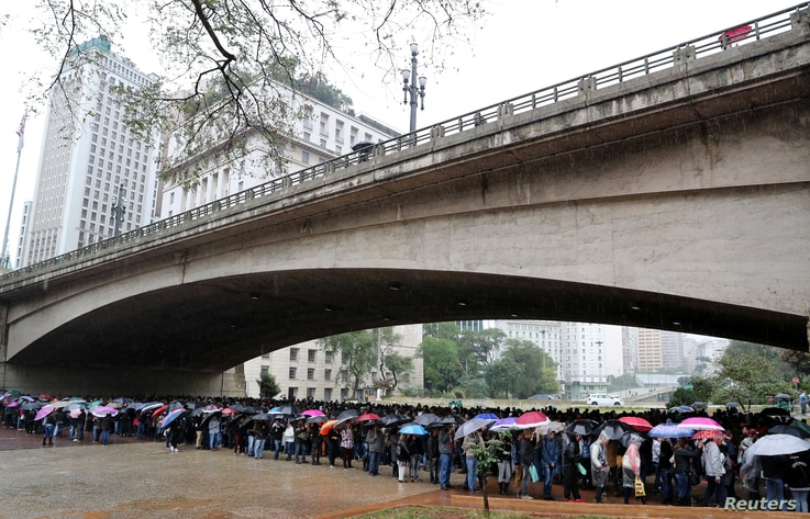 Unemployed people line up to fill out applications while looking for job opportunities in downtown Sao Paulo, Brazil, Aug. 6, 2018.