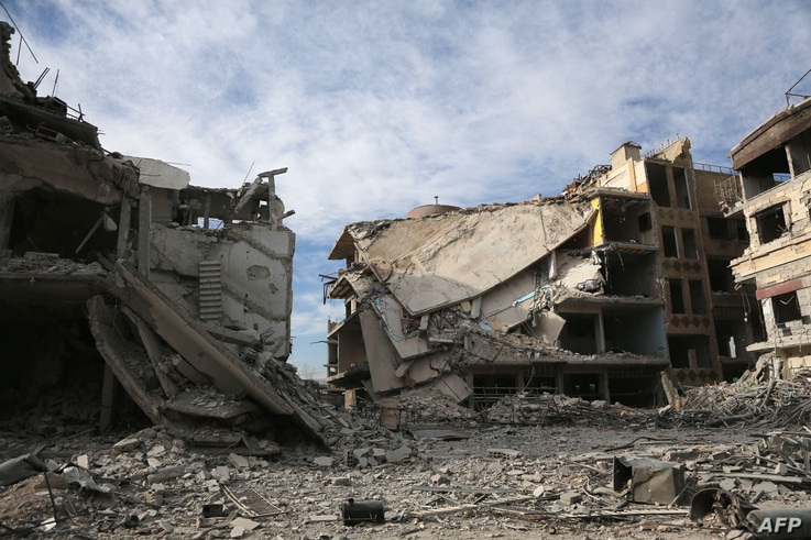 Buildings destroyed during various Syrian government bombardments are seen in the rebel-held town of Hamouria in the Eastern Ghouta region on the outskirts of Damascus, March 13, 2018.