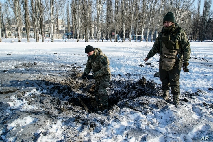 A Ukrainian soldier inspects a crater left by an explosion in Avdiivka, Ukraine, Jan. 31, 2017.