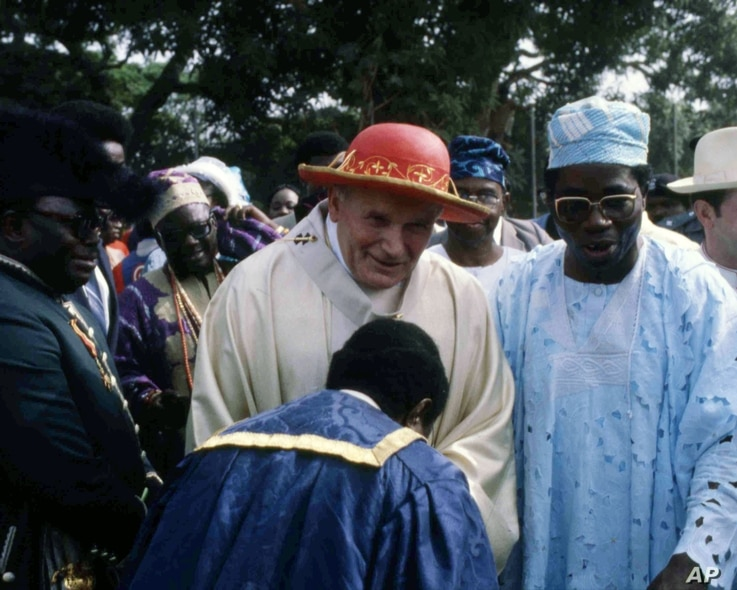 Pope John Paul II is greeted by an official during a visit to Ibadan, Nigeria, Feb. 15, 1982.
