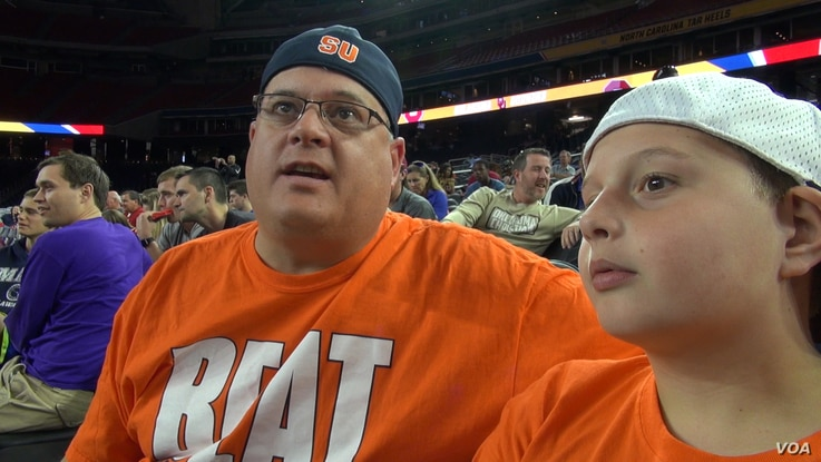 """Twelve-year-old Tyler Hathaway and his father, Eric, came all the way from Rochester, New York, to support the Syracuse team at the Final Four in Houston, Texas. It's a """"huge opportunity,"""" Eric says. (G. Flakus/VOA)"""