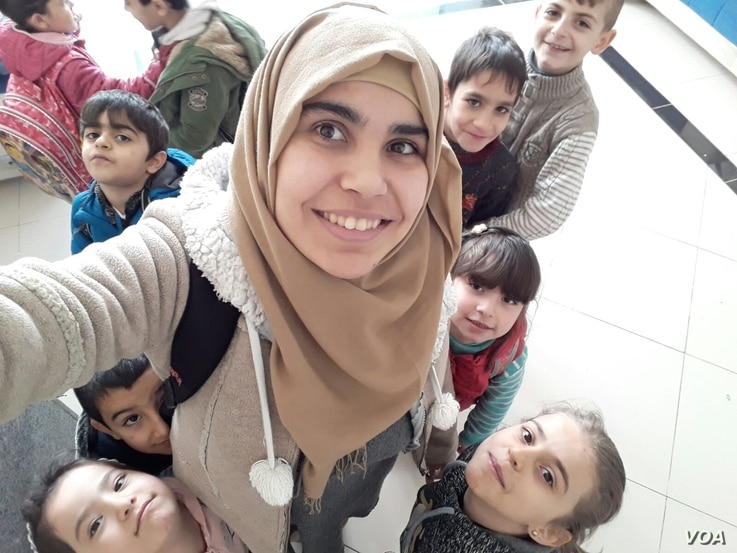Shahira Qaddour smiles for a picture with the children in Selam Orphanage. (M. Qarra)