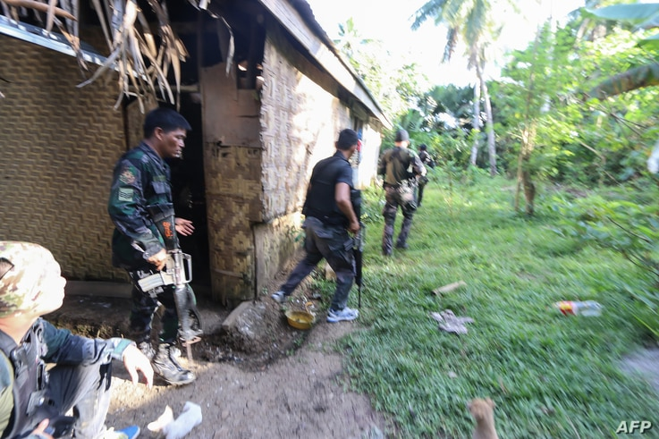 Police and soldiers take position as they engage with the Abu Sayyaf group in the village of Napo, Inabanga town, Bohol province, in the central Philippines on April 11, 2017.
