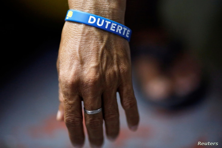 FILE - An inmate who is about to be released wears a wristband with the name of Philippine President Rodrigo Duterte at Quezon City Jail in Manila, Philippines, Oct. 18, 2016.