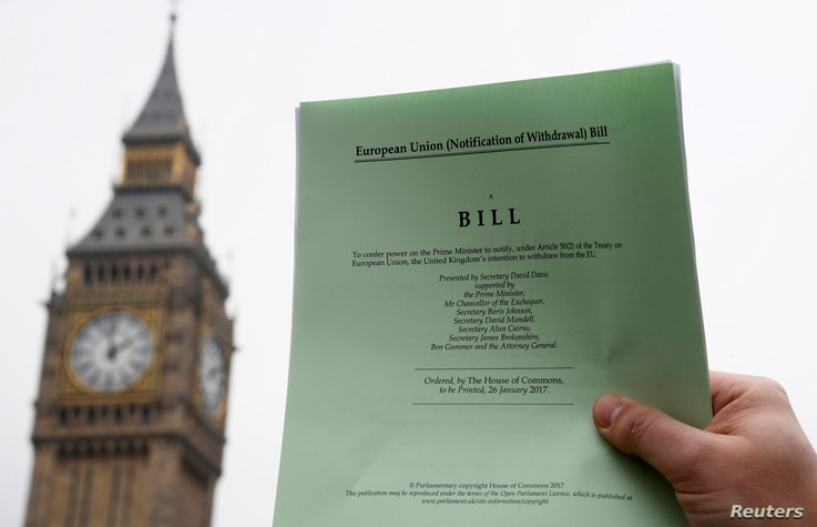 A journalist poses with a copy of the Brexit Article 50 bill, introduced by the government to seek parliamentary approval to start the process of leaving the European Union, in front of the Houses of Parliament in London, Jan. 26, 2017.