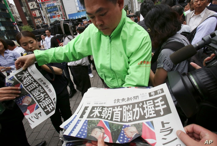 A staff of a Japanese news paper Yomiuri distributes an extra edition of the newspaper reporting about the summit between U.S. President Donald Trump and North Korean leader Kim Jong Un in Singapore, at Shimbashi Station in Tokyo, June 12, 2018.
