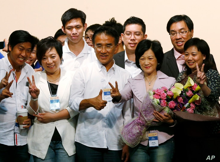 FILE - Former Hong Kong Secretary of Security Regina Ip, second from right in front, and Michael Tien, third from right in front, from the New People's Party celebrate after winning seats on the Legislative Council in Hong Kong, Sept. 10, 2012.