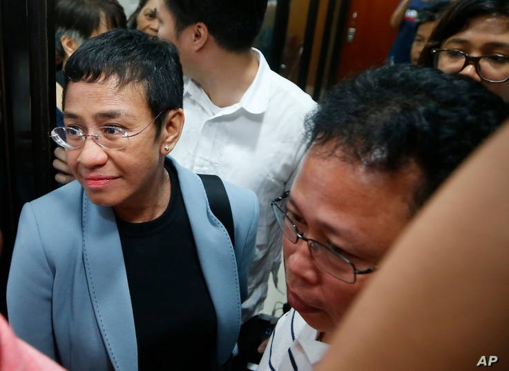 Maria Ressa, the award-winning head of a Philippine online news site Rappler that has aggressively covered President Rodrigo Duterte's policies, is escorted into another room following her arrest by National Bureau of Investigation agents in a libel ...