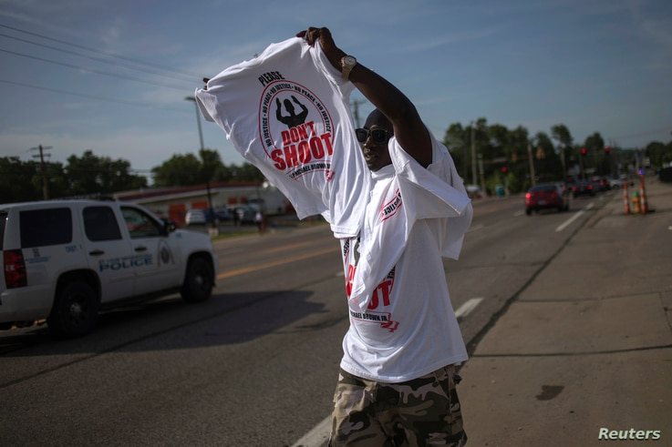 A man sells T-shirts along the roadside in Ferguson, Missouri August 21, 2014. Missouri's governor ordered the withdrawal of National Guard troops from the strife-torn town of Ferguson on Thursday as tensions appeared to ease after nearly two weeks o...